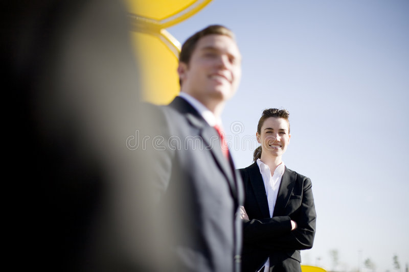 Businesspeople. Three businesspeople in a row with businesswoman standing looking at the camera with her arms crossed royalty free stock image