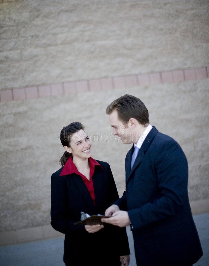 Businesspeople. Businessman and businesswoman standing working together discussing stock images