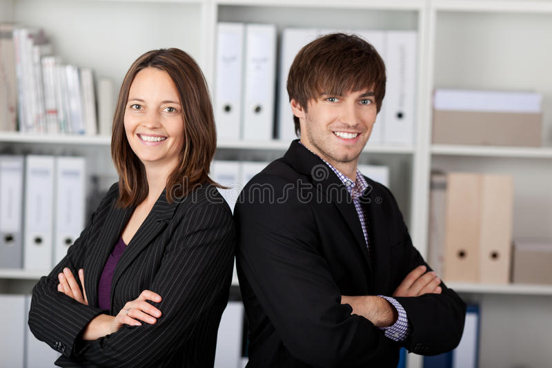 Businesspeople With Arms Crossed Standing In Office stock images