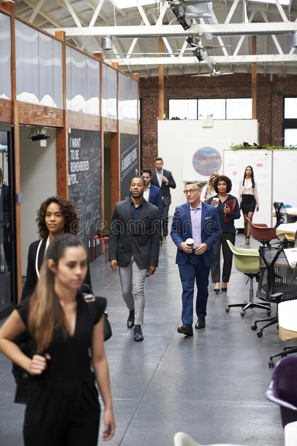 Businesspeople Arriving For Work In Busy Modern Open Plan Office stock photography
