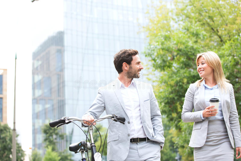 Businesspeople with bicycle and disposable cup conversing while walking outdoors royalty free stock images