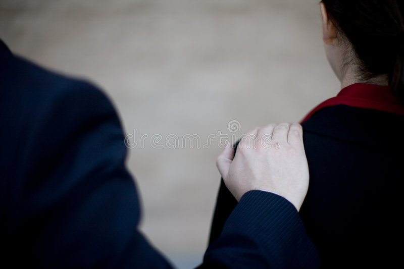 Businesspeople care. Rear view of businessman placing hand on shoulder of businesswoman stock photos