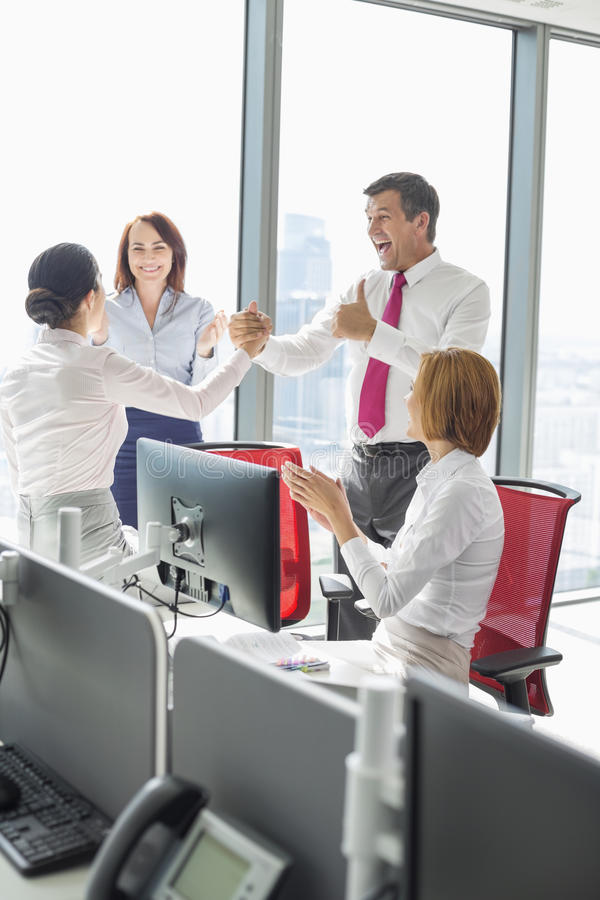 Businesspeople celebrating success in office stock images
