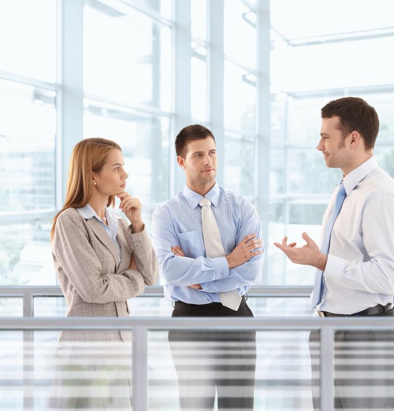 Businesspeople chatting in modern office lobby royalty free stock photos