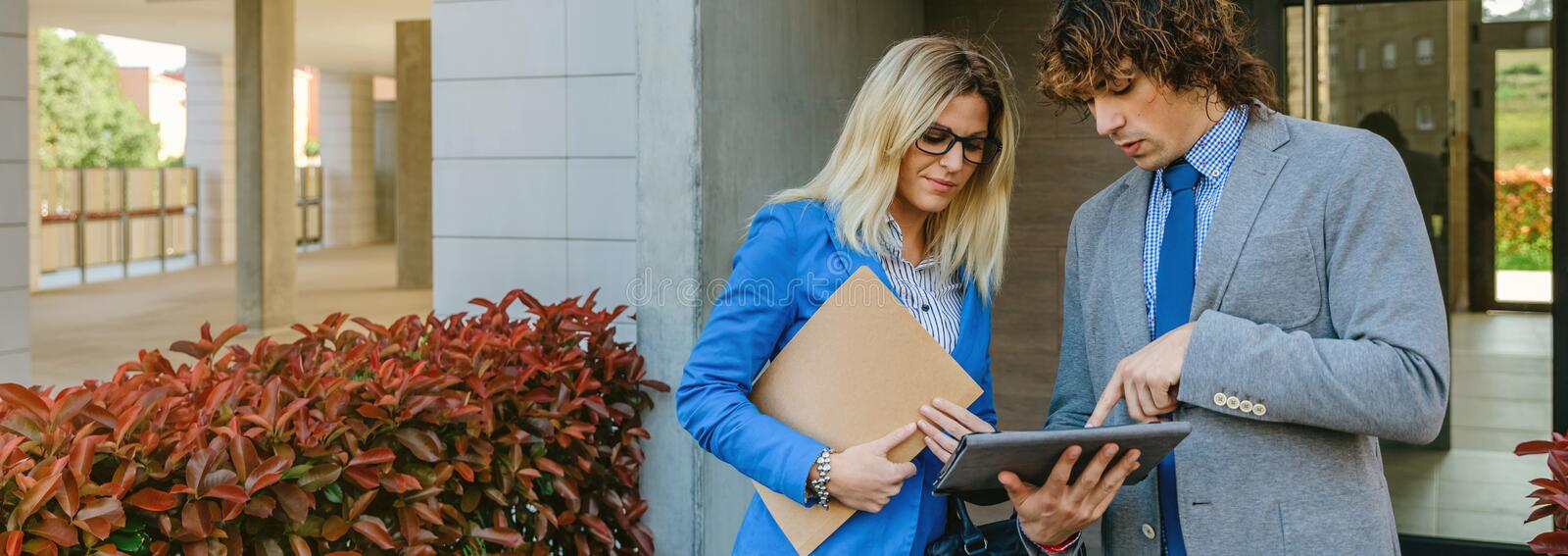 Businesspeople checking documents in the street stock images