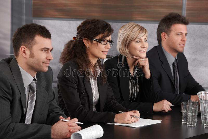 Businesspeople conducting job interview. Panel of friendly businesspeople sitting at meeting table conducting job interview royalty free stock photo