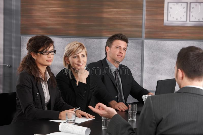 Businesspeople conducting job interview. Panel of friendly businesspeople sitting at meeting table conducting job interview listening to applicant stock photos
