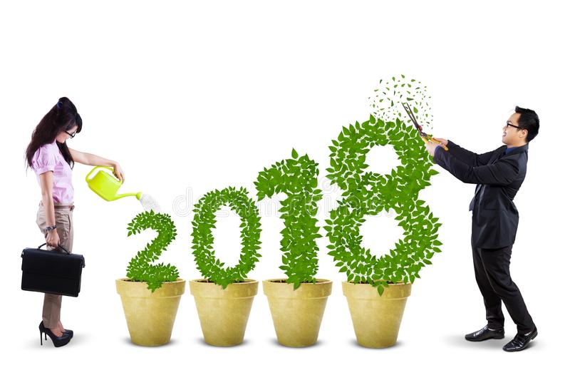 Businesspeople cutting and watering tree shaped number 2018 stock photography