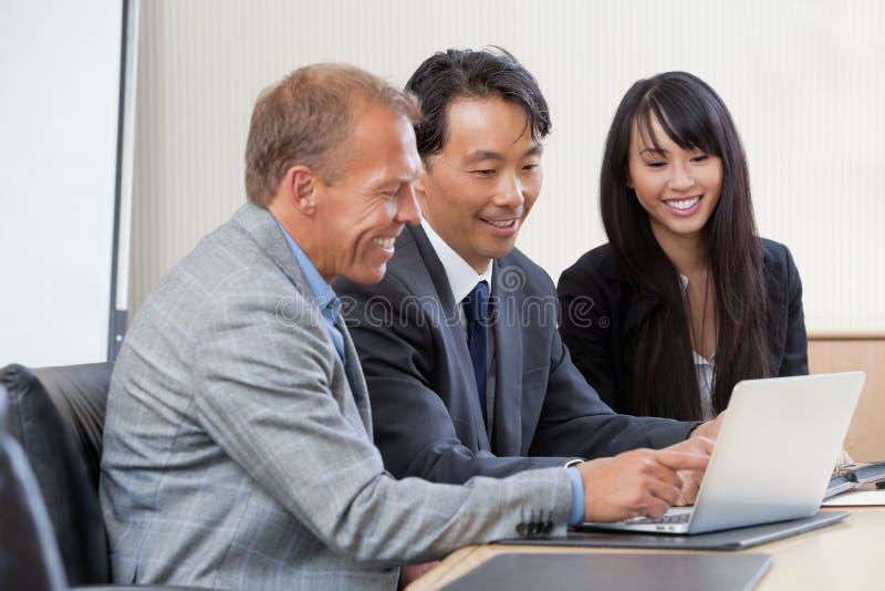 Businesspeople die aan laptop werkt stock fotografie