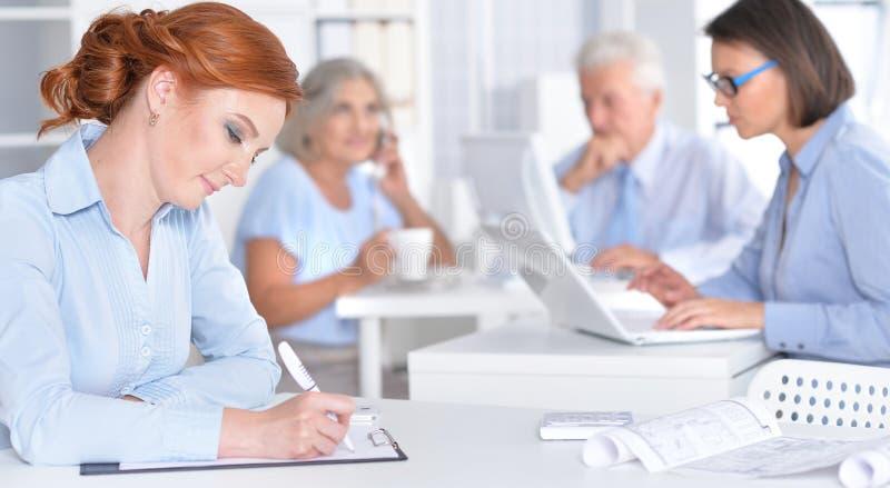 Businesspeople die in bureau werkt stock afbeeldingen