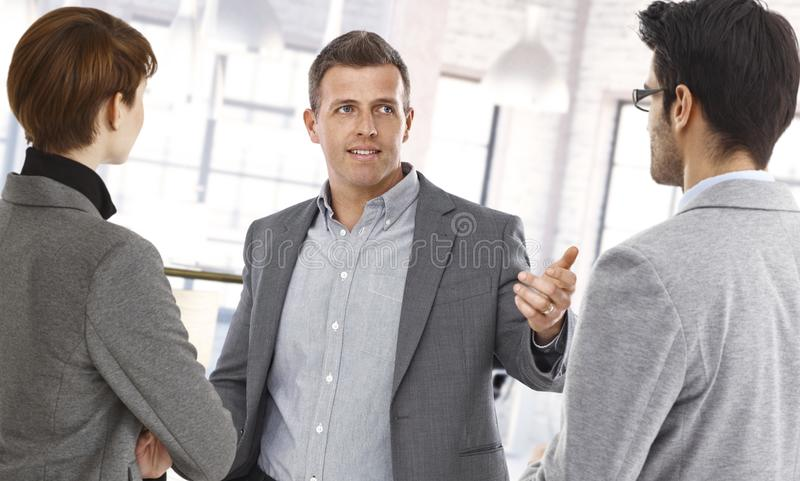 Businesspeople discussing at office. Happy businesspeople discussing at office stock image