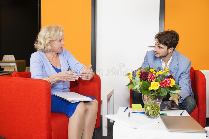 Businesspeople Discussing At Office Lobby stock photography