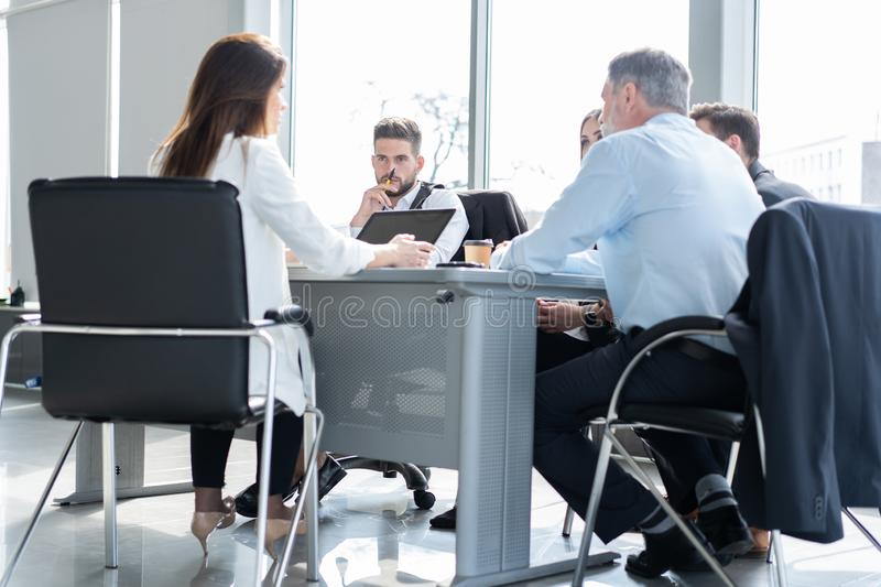 Businesspeople discussing together in conference room during meeting at office. stock photography