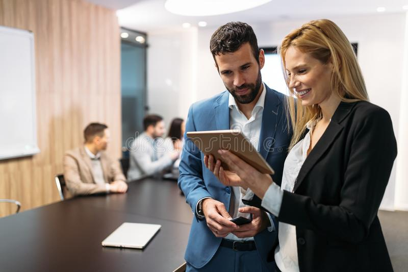 Businesspeople discussing while using digital tablet in office stock image