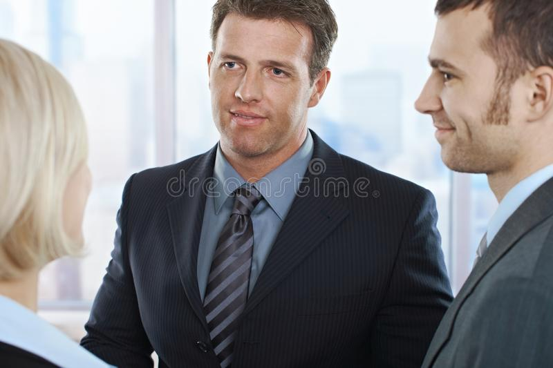 Businesspeople in discussion. Businessmen looking at businesswoman standing in office, smiling stock photos