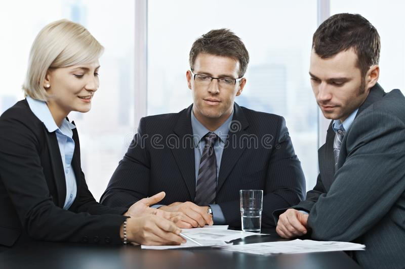 Businesspeople at discussion. Mid-adult professionals at businessmeeting, looking at documents deep in discussion royalty free stock photos