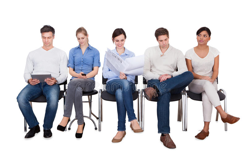 Businesspeople doing various activities on chairs. Full length of businesspeople doing various activities while sitting on chairs against white background royalty free stock image