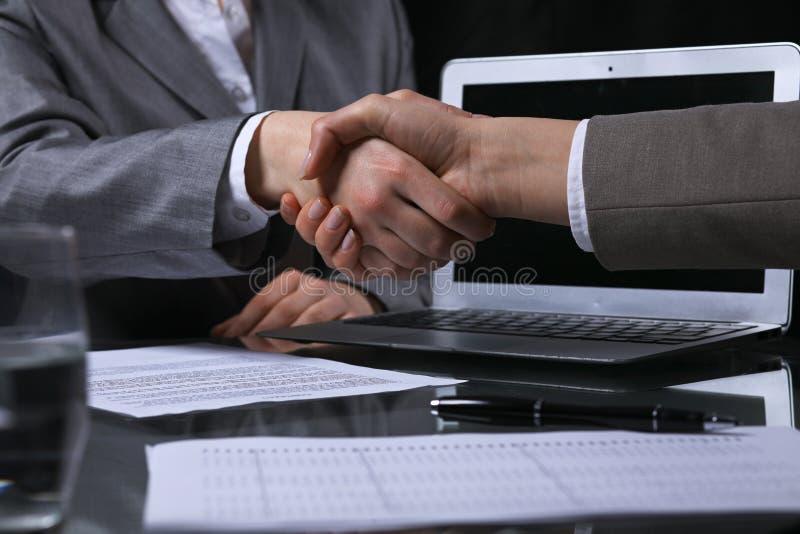 Businesspeople eller advokater som skakar händer på ändlöst möte Låg key lighting arkivbilder