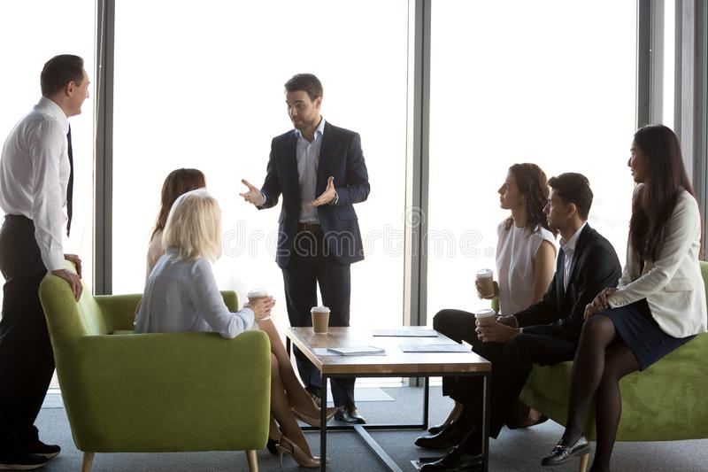 Businesspeople enjoy coffee talking during informal office meeting royalty free stock photos