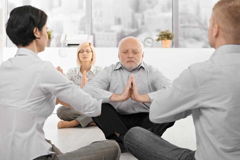 Businesspeople exercising yoga in office stock photography