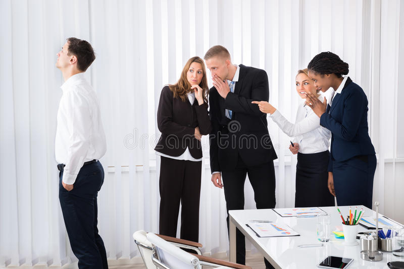 Businesspeople Gossiping In Office. Businesspeople Gossiping Behind Young Colleague In Office stock images