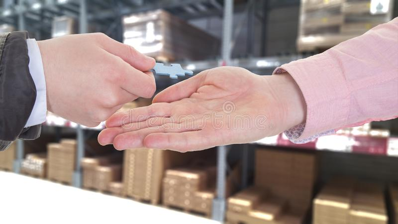 Businesspeople hands exchanging a puzzle piece in a warehouse royalty free stock photography