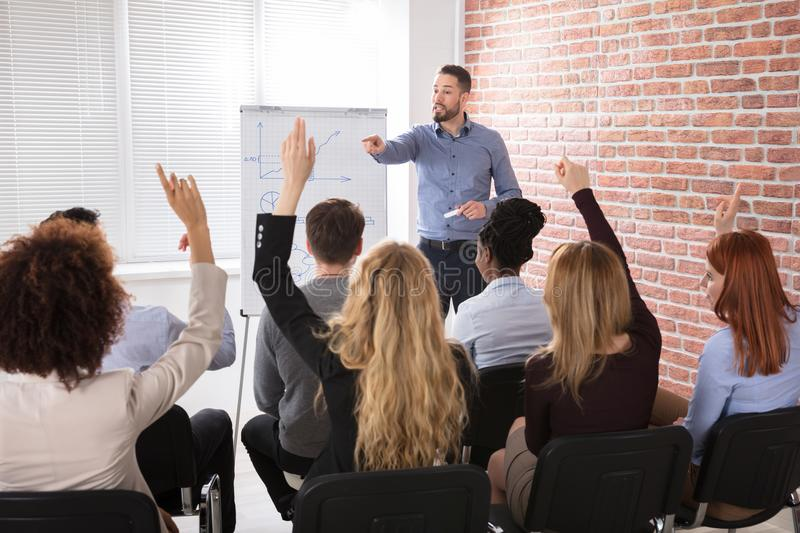 Group Of Businesspeople Raising Hands In Conference stock photography