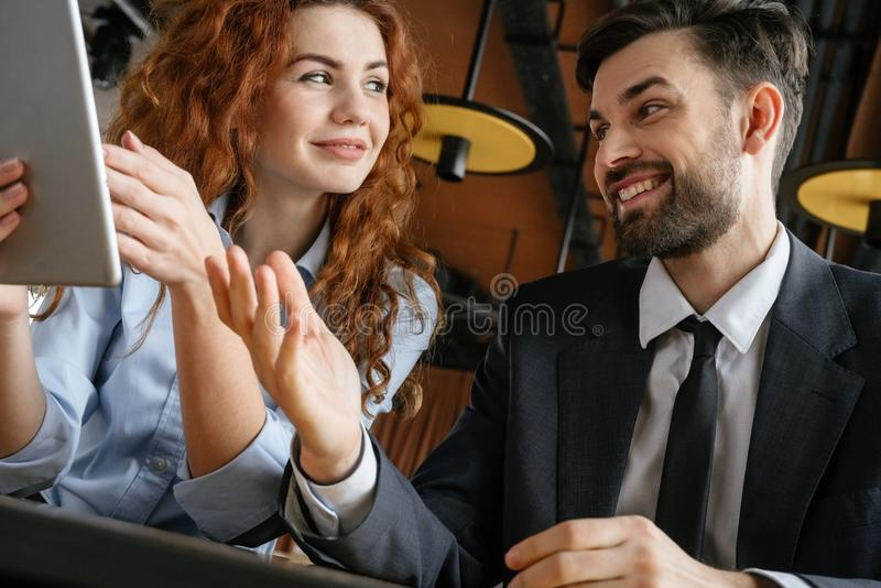 Businesspeople having business lunch at restaurant sitting bottom view close-up holding digital tablet smiling royalty free stock image