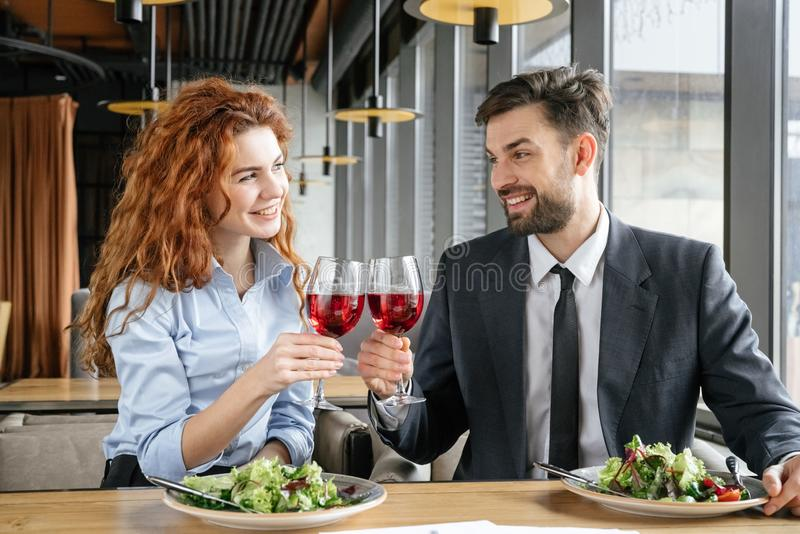 Businesspeople having business lunch at restaurant sitting eating salad drinking wine smiling playful cheers royalty free stock image