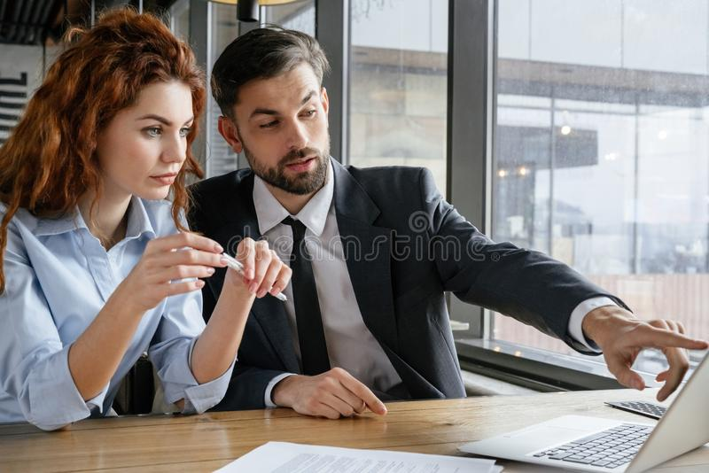 Businesspeople having business lunch at restaurant sitting man asking woman question pointing at laptop stock images