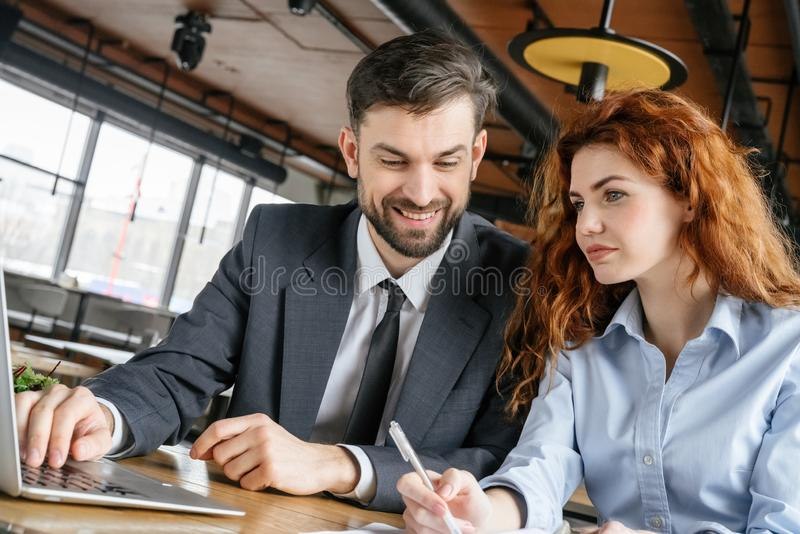 Businesspeople having business lunch at restaurant sitting man browsing laptop looking at woman taking notes stock photo