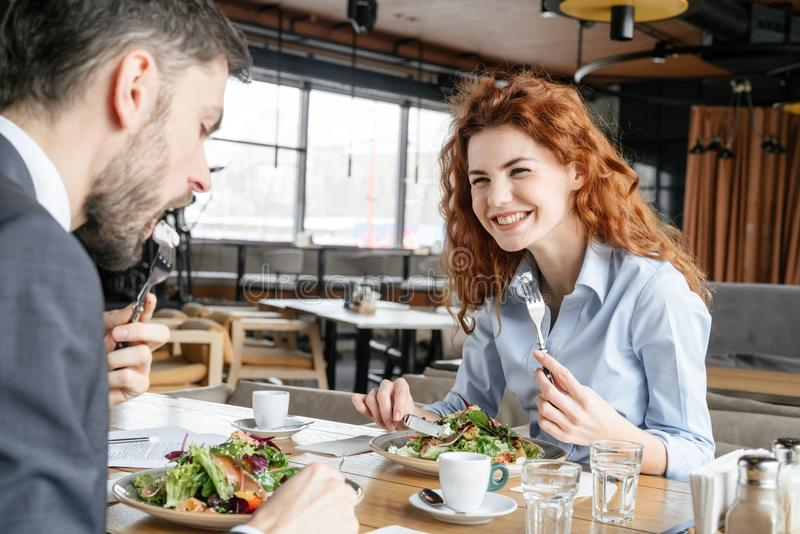 Businesspeople having business lunch at restaurant sitting man eating salad concentrated while woman laughing stock photo