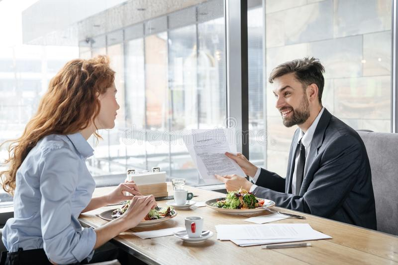 Businesspeople having business lunch at restaurant sitting near window eating salad discussing project cheerful royalty free stock photos