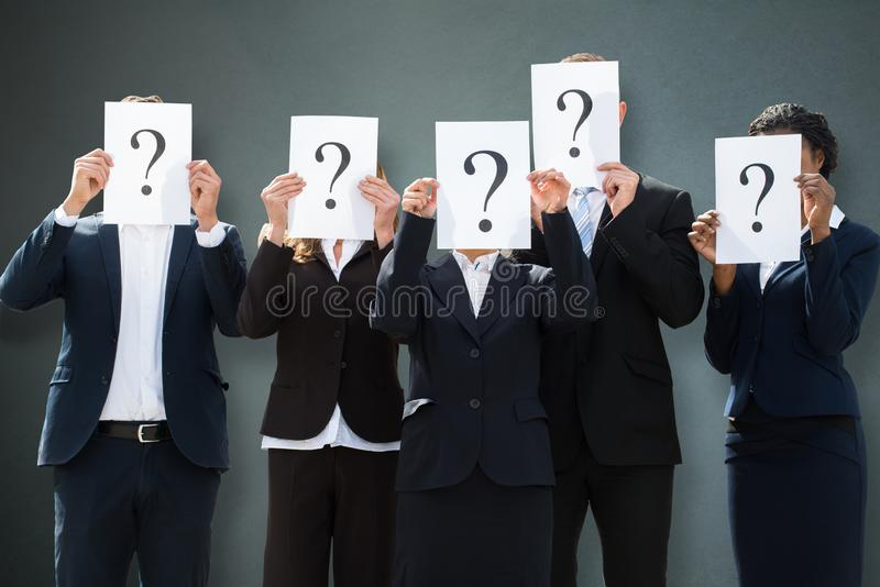 Businesspeople Hiding Their Faces Behind Question Mark Sign stock photography