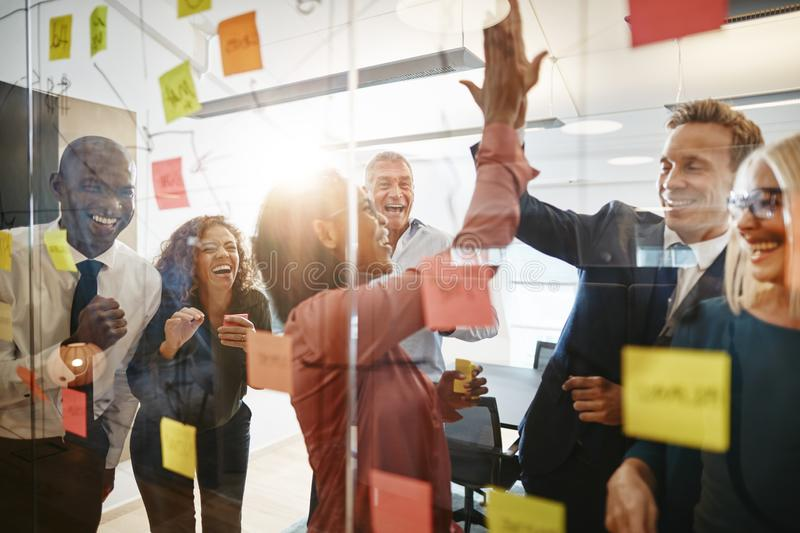 Businesspeople high fiving together with colleagues in an office stock photos