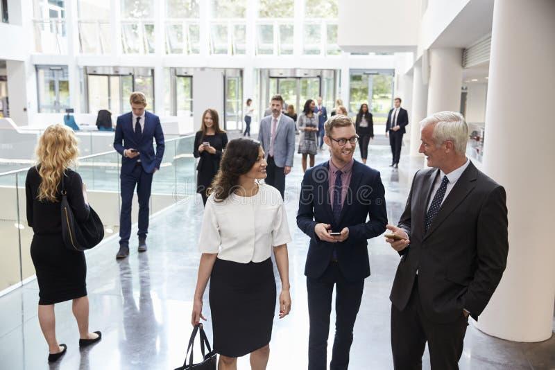 Businesspeople i upptaget lobbyområde av det moderna kontoret royaltyfria bilder