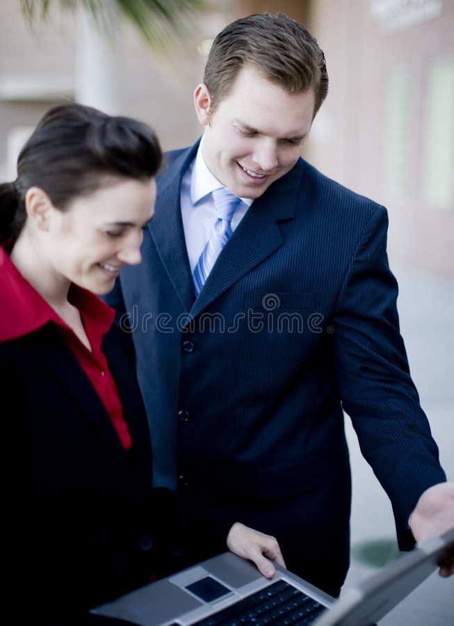 Businesspeople laptop. Businessman and businesswoman in formal wear looking down at laptop screen royalty free stock photography