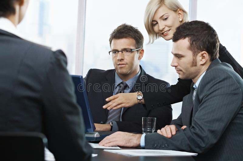 Businesspeople looking at laptop. Businessmen looking at laptop, businesswoman pointing at screen in office, at meeting table stock photography
