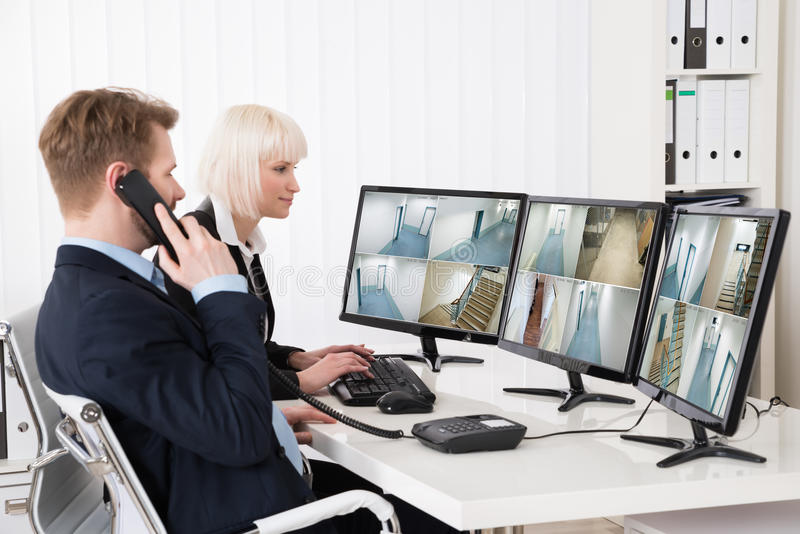 Businesspeople Looking At Multiple Camera Footage stock image