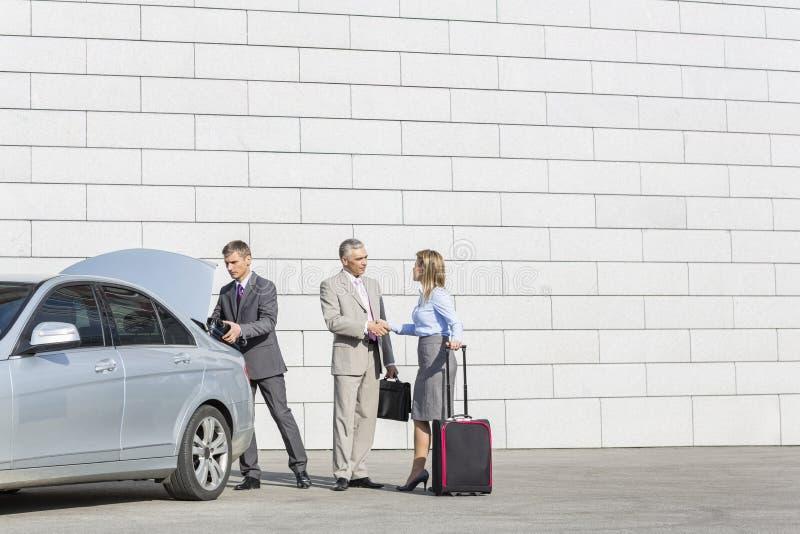 Businesspeople med bagage som skakar händer utanför bilen på gatan royaltyfri fotografi