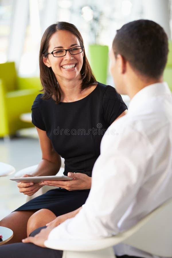 Businesspeople med den Digital tableten som har InOffice möte royaltyfria foton