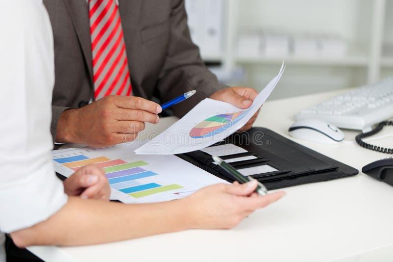 Businesspeople med grafer på kontorsskrivbordet royaltyfri foto