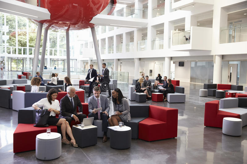 Businesspeople Meeting In Busy Lobby Of Modern Office stock image