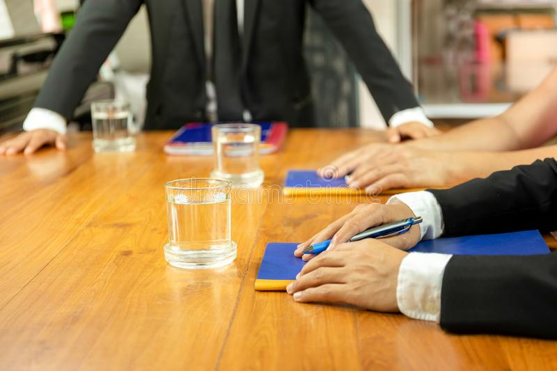 Businesspeople meeting at conference with glass of wter and notebook on wooden table. Businesspeople meeting at conference with glass of wter and notebook on stock photos