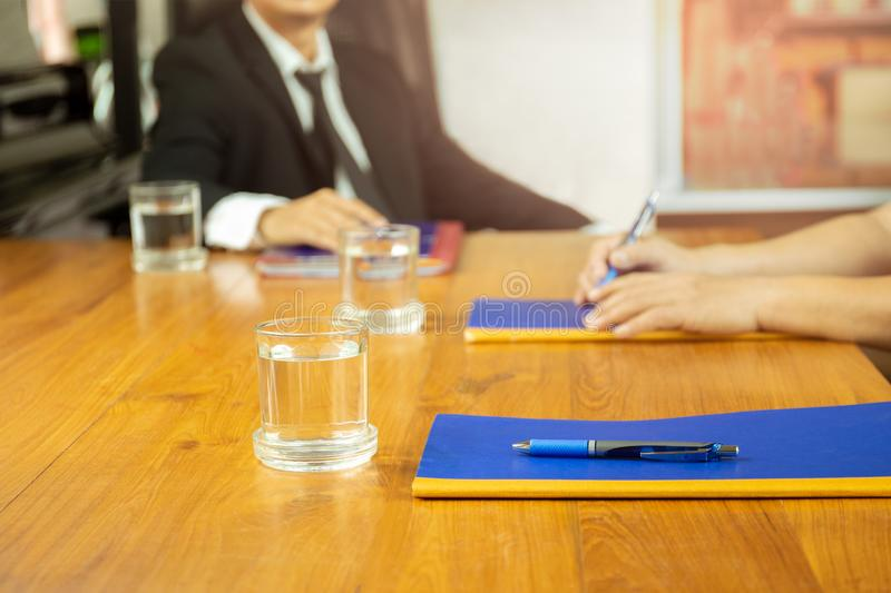 Businesspeople meeting at conference with glass of wter and notebook on wooden table. Businesspeople meeting at conference with glass of wter and notebook on royalty free stock photo