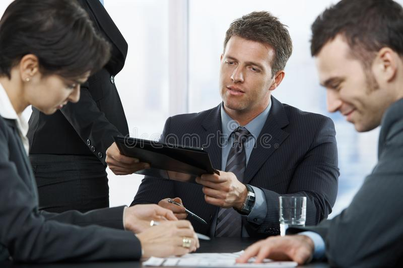Businesspeople at meeting. Executive getting report at meeting from assistant, other colleagues sitting looking down on documents royalty free stock photography