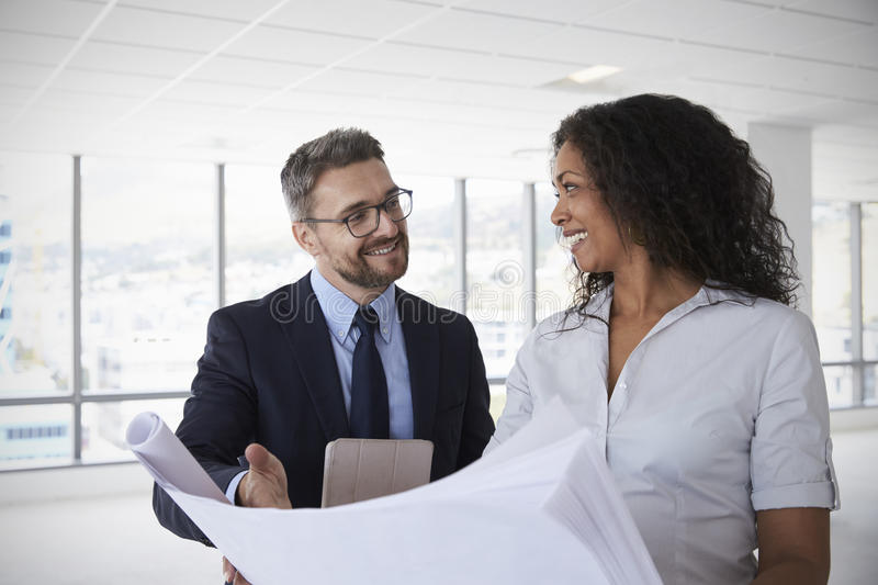 Businesspeople Meeting To Look At Plans In Empty Office royalty free stock images