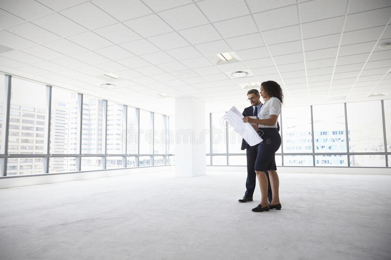 Businesspeople Meeting To Look At Plans In Empty Office royalty free stock photography