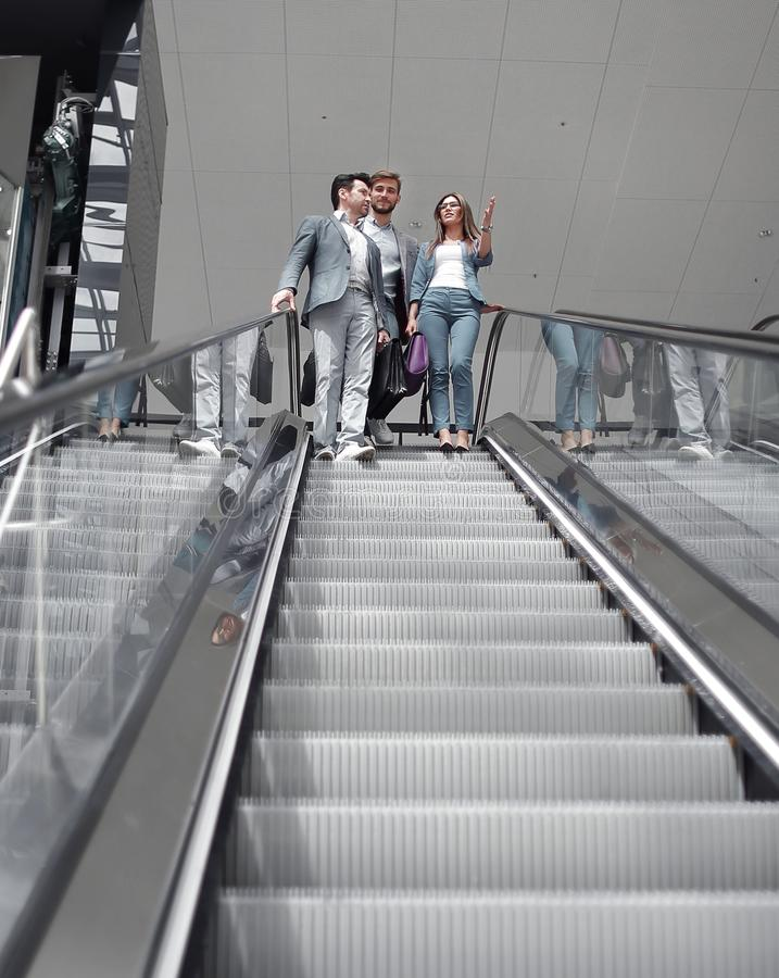 Businesspeople moving down on escalator in office royalty free stock photography