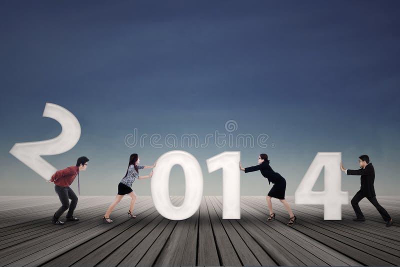Businesspeople ordnar det nya året 2014 arkivfoto